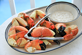 stone crab claws with cracker and sauce bowl on ceramic plate